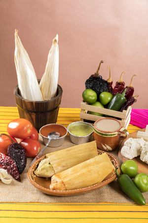 Typical Mexican food dishes with sauces on colorful table. Tamales of red and green mole. Guadalajara Mexico.