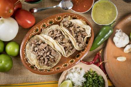 Typical Mexican food dishes with sauces on colorful table. Tacos of roasted meat in clay dish.