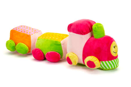 Colorful stuffed train with shadow sitting on white background.