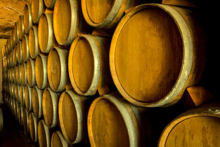 Wine barrels stacked in the old cellar of the winery. Foto de archivo