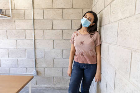 Young woman with mouth mask from COVID-19 epidemic alone in empty building under construction.