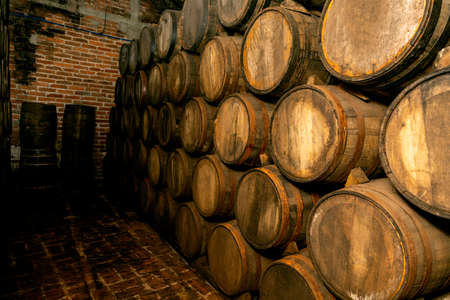 Wine barrels stacked in the old cellar of the winery. Stock fotó
