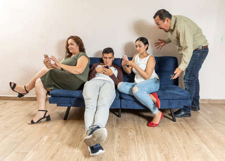 Group of youths and matures during COVID-19 disease quarantine playing in cellphones. Angry dad