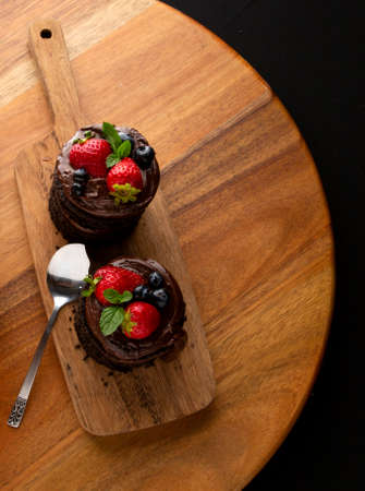 Delicious chocolate cupcake with strawberries and blackberries on elegant wooden table.