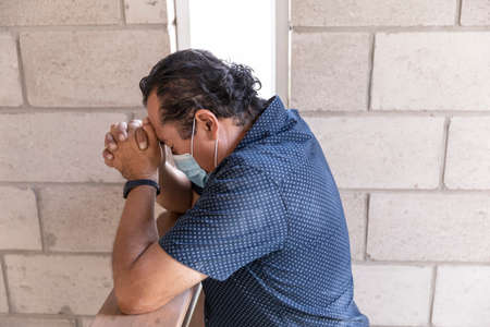 Man praying with face mask, during virus pandemic in prayer chapel. Holy Trinity. Divine Providence. Stock Photo