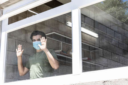 Man in quarantine with face masks looking out of their house through the window. Stock Photo