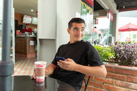 Smiling and handsome young man drinking coffee in the mall with his cellphone
