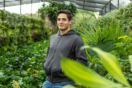 Portrait of young entrepreneur proud owner of nursery or business .. Growing house of decorative plants and vegetables.