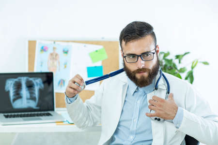 Healthy and happy doctor with stetoscope on his office