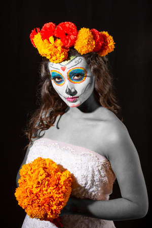 Beautiful Mexican woman with wedding dress and makeup Catrina in black background Banco de Imagens