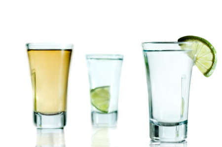 Tequila shots with lemon and reflection on bright table.