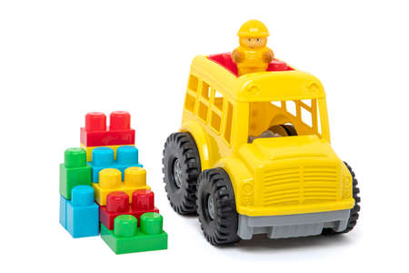 Toys, yellow truck with plastic blocks on white background.