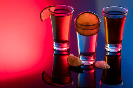 Shot of tequila with salt and lemon and reflection on bright table. Bar with colored lights.