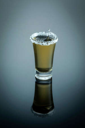Shot of tequila with salt and lemon and reflection on bright table.
