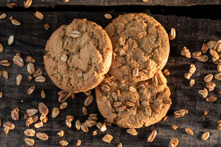 Homemade cookies with whole grain oatmeal and spoon on rustic wooden table.