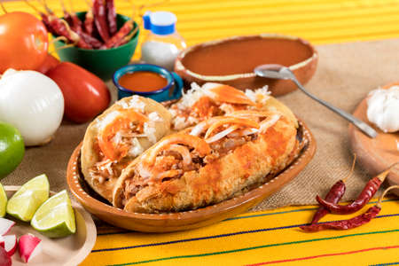 Typical Mexican food dishes with sauces on colorful table.