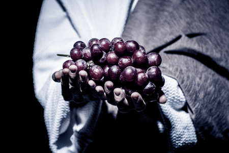 Jesus Christ praying to God consecration the bread and grapes in the dark black night. Black and white Banque d'images