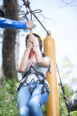 Girl pulling the zip line in the forest of Mazamitla