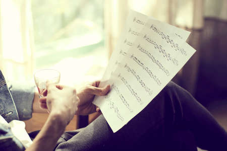 Casual detail indoor of a person reading sheet music