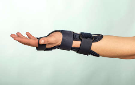 Man hand with adjustable immobilizer for injuries of bones and muscles .. Orthopedic device.human, dark, Banco de Imagens