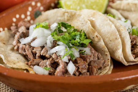 Typical Mexican food dishes with sauces on colorful table. Roast beef tacos detail.
