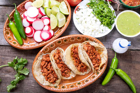 Tacos of meat to the shepherd or marinated. Typical mexican food in a rustic table full of sauces and vegetables.