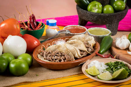 Tacos of roast beef. Typical Mexican food of Guadalajara, rustic table full of sauces and vegetables.
