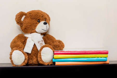 Teddy bear soft toy in child's bedroom with colorful books Archivio Fotografico
