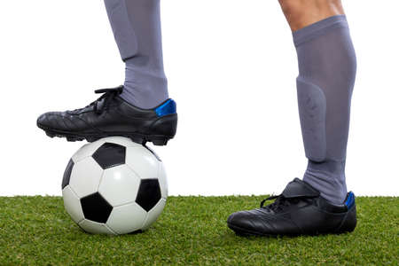 detail of soccer player feet stepping on a ball over the grass on white background