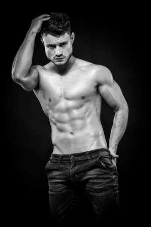 Young muscular shirtless man with denim shorts on dark background Foto de archivo