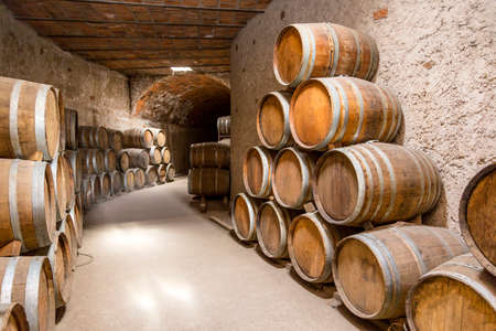 Wine barrels stacked in the old cellar of the winery. Reklamní fotografie