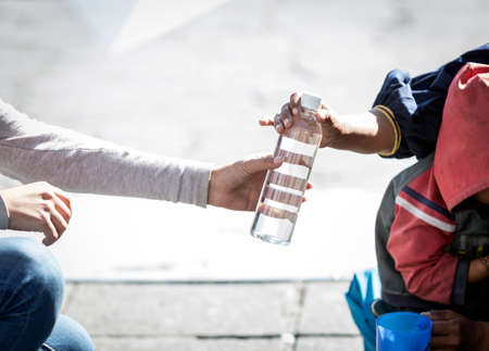 Detail of woman's hand giving a bottle of water to a homeless person Foto de archivo