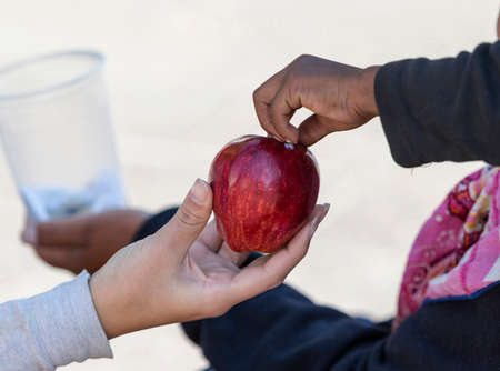 Detail of woman hand giving a red apple to a homeless boy. Foto de archivo