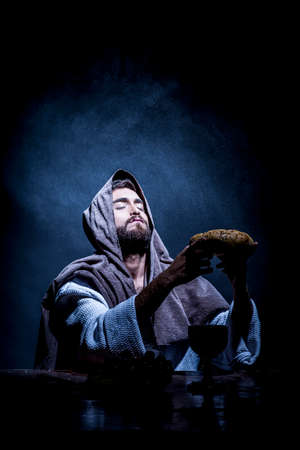 Jesus Christ praying to God consecration the bread and grapes in the dark black night. Banque d'images