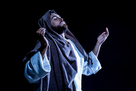 Jesus Christ praying to God consecration the bread and grapes in the dark black night.