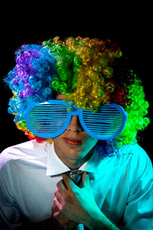 man with glasses and wig playing the piano. Clown.