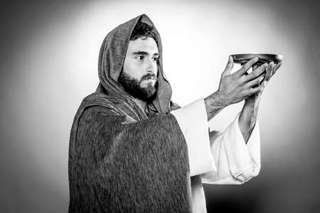 Jesus Christ praying to God consecration the bread and wine in the dark black night Banque d'images