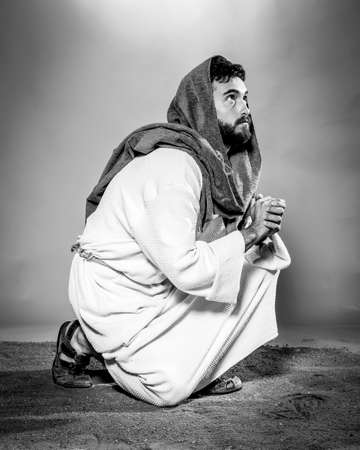 Jesus Christ praying to God with open arms in the dark black night. Black and white. Banque d'images