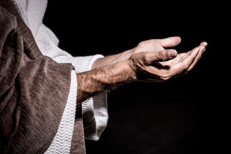 Jesus Christ praying to God consecration the bread and grapes in the dark black night. Black and white Stock Photo