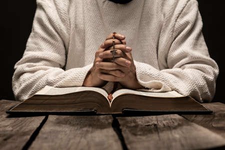 Jesus Christ praying to God with the Holy Bible and the Holy Rosary in the hands in the dark black night