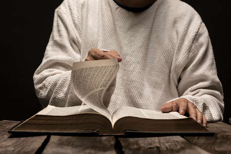 Jesus Christ Praying and reading the Holy Bible in the dark black night