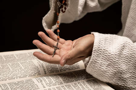 Jesus Christ praying to God with the Holy Bible and the Holy Rosary in the hands in the dark black night Banque d'images