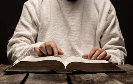 Jesus Christ Praying and reading the Holy Bible in the dark black night Banque d'images