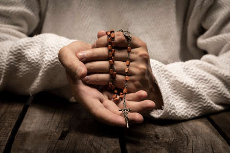 Jesus Christ praying to God with the Holy Rosary in hands in the dark black night Banque d'images