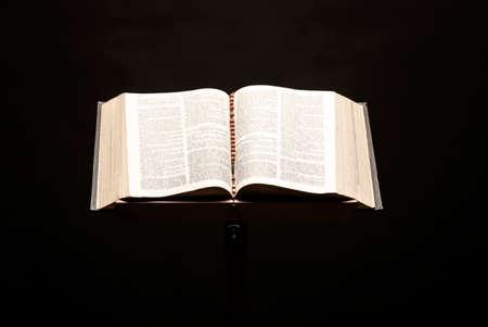 Holy Bible open on pedestal on black background