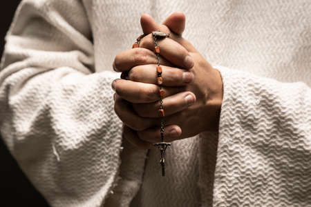 Jesus Christ praying to God with the Holy Rosary in hands in the dark black night