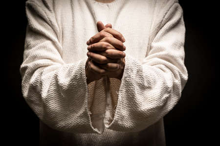 Jesus Christ praying to God with open arms in the dark black night Banque d'images
