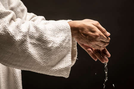 Water for Baptism pouring out of the hands of Jesus Christ during a dark night.