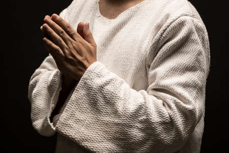 Jesus Christ praying to God with open arms in the dark black night