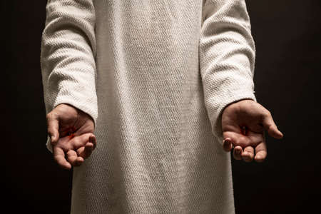 Jesus of Nazareth showing the wounds on his hands while praying on a dark night after being resurrected. Banque d'images